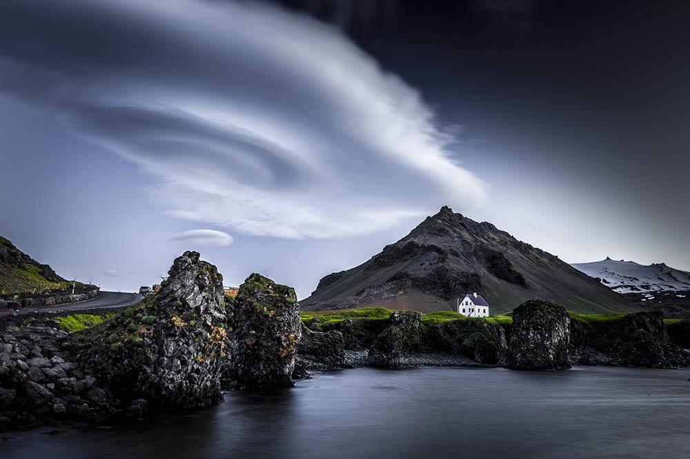 Nube con forma de OVNI sobrevolando una casa en el lago